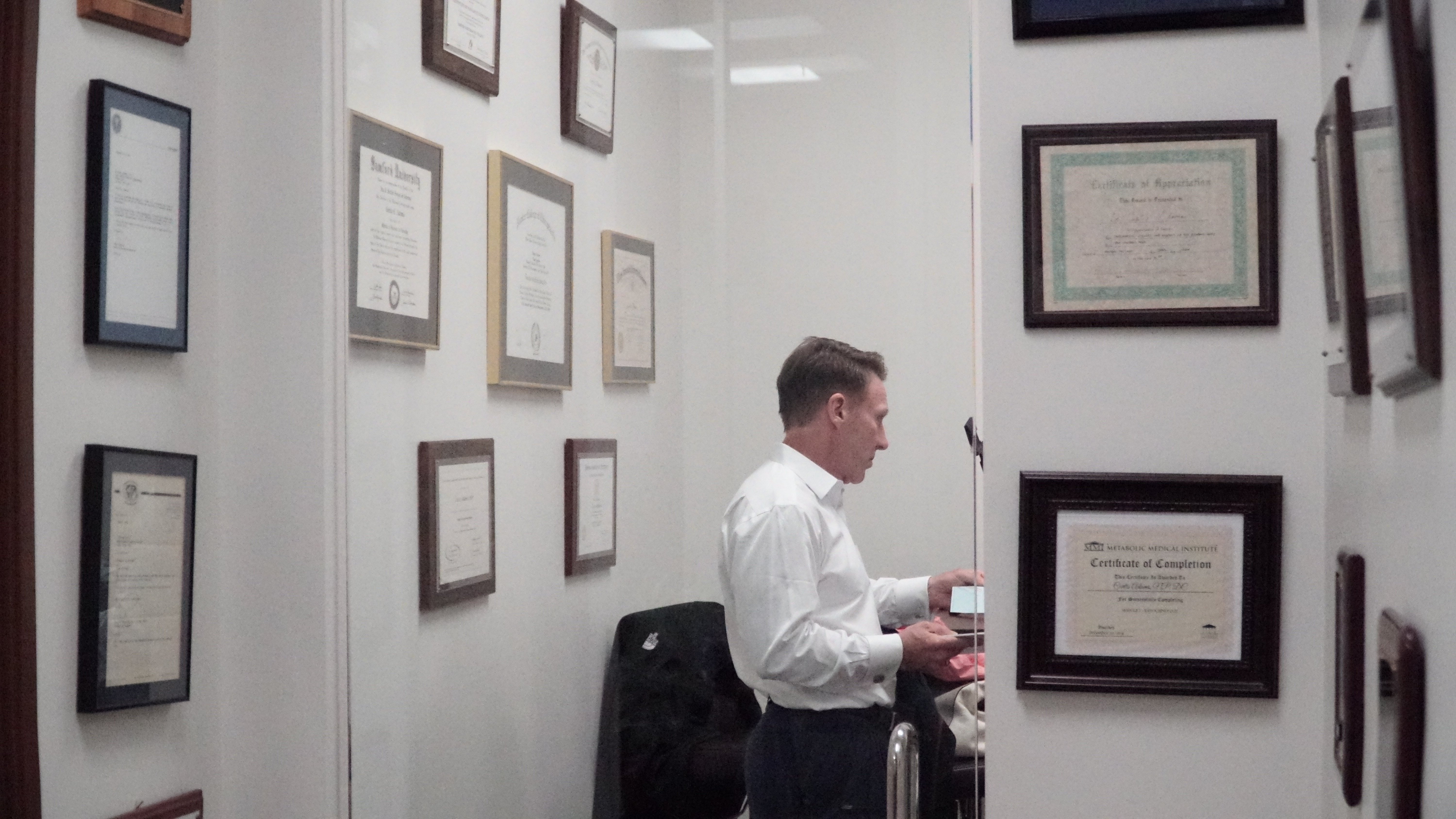 Dr. Adams of Progressive Integrated Healthcare Dallas standing by his wall of plaques and certifications